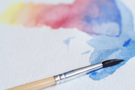 Close-up of beautiful watercolor brushstrokes on a white sheet, a brush in the picture, background or concept