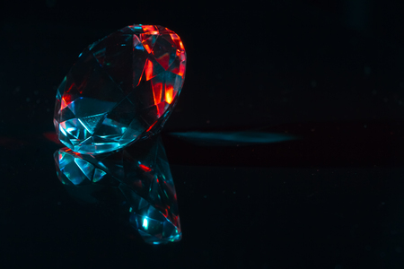 Closeup of a diamond on a black mirror surface with red and blue highlights, background or concept Stok Fotoğraf