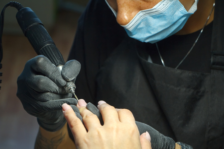 Beautician grinds the nail bar for a manicure in the beauty salon. Finger nail treatment, grinding and polishing. Manicurist Hands Make Female manicure in the nail Salon.