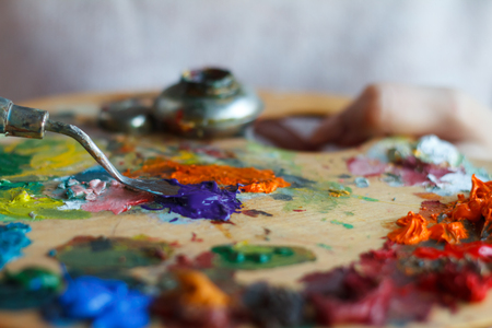Close-up of female hands mixing paints on a palette with a spatula against a white canvas, creating an oil painting, soft focus