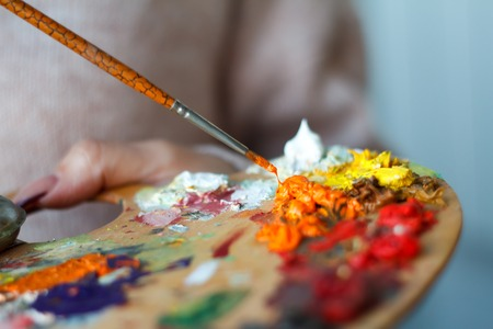 Closeup of palette with colorful paints and brush on white surface, background or concept