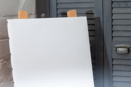 An easel with a clean white canvas is ready for work against a white brick wall, background or concept about art.