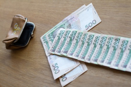 The arrow from the bills of the Ukrainian currency shows the direction in a small wallet, a business concept about the receipt of money Stok Fotoğraf