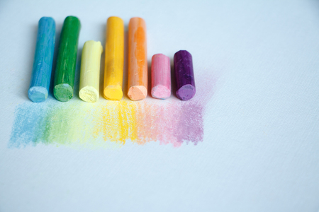 Close up view of the colorful chalk pastels on the white background, soft focus