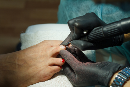 Beautician grinds the nail bar for a pedicure in the beauty salon. Finger nail treatment, grinding and polishing. Manicurist Hands Make Female pedicure in the nail Salon. Stok Fotoğraf