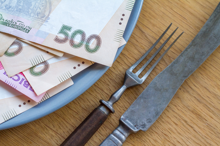 Closeup of Ukrainian money lying on a plate with a fork and knife, business concept