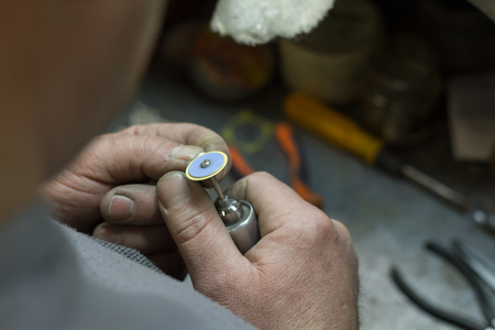The master jeweler holds the working tool in his hands and makes jewelery at his workplace in the jewelry workshop. Stok Fotoğraf