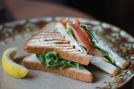 Closeup of sandwich with smoked salmon creamcheese and greens on a beautiful plate, background or concept on the breakfast theme Stok Fotoğraf