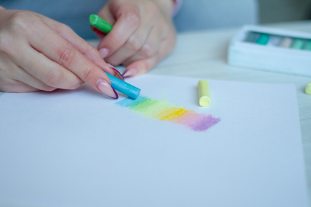 Close-up of female hands are drawing with multicolored chalks on a white sheet, a box with crayons is standing nearby