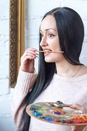 Closeup of a young woman with black hair mixes paint on a palette with a brush against a background of an empty vintage frame, creating an oil painting, soft focus Reklamní fotografie