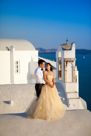 Greece, Santorini, Oia. September 16, 2014: a couple of newly married people in beautiful attire enjoying their honeymoon months in Greece. Editorial