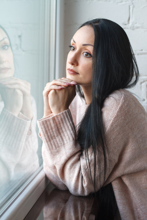 Beautiful young woman with long black hair looks out the window, reflected in the window, background or waiting concept, soft focus Foto de archivo