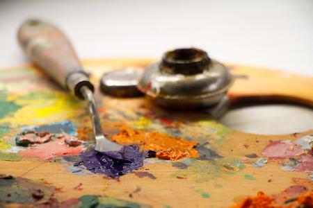 Nahaufnahme der Palette mit bunten Farben und Spachtel auf weißer Oberfläche, Hintergrund oder Konzept