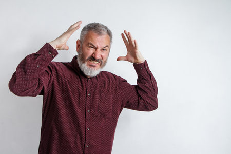 Closeup portrait of angry upset gray bearded man, worker, employee, business man hands in air, open mouth yelling isolated on white background. Negative emotions, facial expression reaction