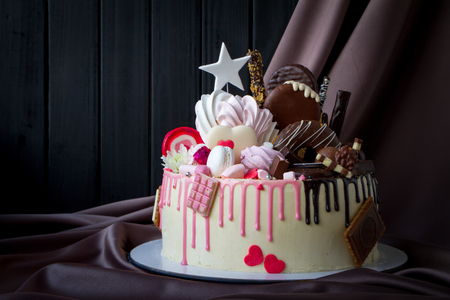 Closeup of black and white chocolate sponge cake with pink and chocolate decoration against the background of fabric drapery Imagens