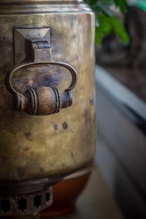 Closeup of a wooden handle on an antique brass samovar. Selective focus