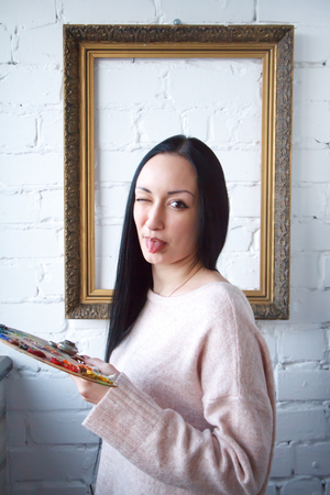 Closeup of a young woman with black hair mixes paint on a palette with a brush against a background of an empty vintage frame, creating an oil painting, soft focus Stock Photo