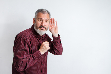 Man bearded hipster hold hand near ear to hear better, eavesdropping and spying, hearing test. Guy try to hear better with hand palm. Hipster with beard and mustache has hearing problems. Stock fotó