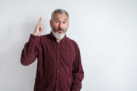 Portrait gray bearded man has an idea, pointing with index finger up isolated on white wall background. Thoughtful guy solved a problem. Face expression, body language, life perception creativity