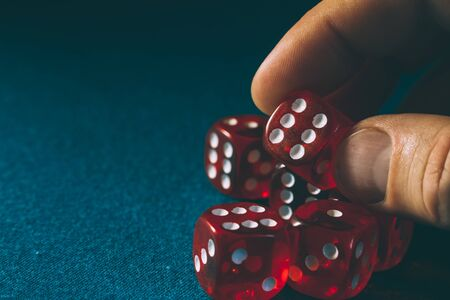 Closeup of hand holding red dice with a winning combination on blue cloth in a casino, concept of winning Stock Photo