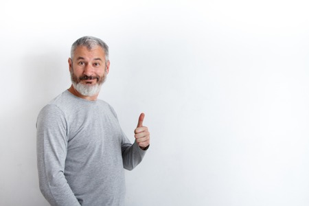 Adult happy gray-haired man with a beard showing thumbs up on a white background, free method for text. Foto de archivo