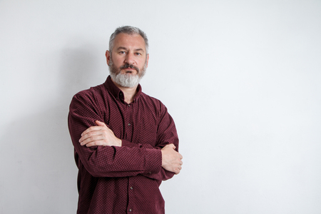 Half-length portrait of a serious gray-haired bearded man in a burgundy shirt on a white background.