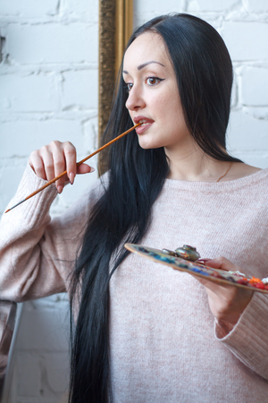 Closeup of a young woman with black hair mixes paint on a palette with a brush against a background of an empty vintage frame, creating an oil painting, soft focus Stok Fotoğraf
