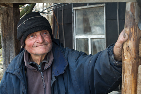 An old man in sloppy clothes stands on the threshold of his own ruined house and looks into the distance, loneliness in the village, life beyond poverty