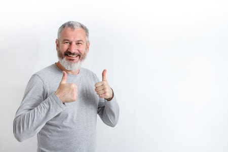 Adult happy gray-haired man with a beard showing thumbs up on a white background, free method for text. Stok Fotoğraf