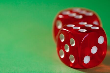 Closeup of a two red dice with a winning number on the top face on a green surface, winning concept