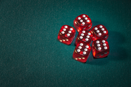 Close-up of several red dice with different digital combinations on green cloth in a casino, concept of winning