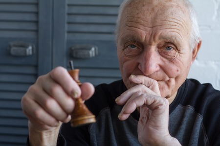 The old man holds in his hands the chess piece of the king, the concept of winning or losing, copyspace