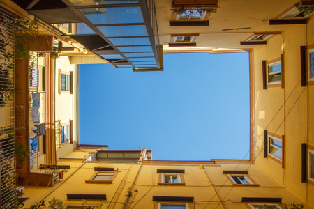 Travel to Italy bottom view of square sky from patio of urban house in Naples over blue sky.