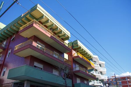 Closeup of part of residential buildings with multi-colored balconies against a blue sky, copyspace Banco de Imagens