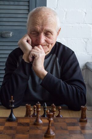 An old man is sitting in front of a chessboard, thinking about the next move in a chess game, copyspace
