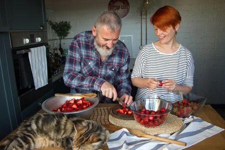Adult couple man and woman peel and cut strawberries for strawberry jam, feed each other, laugh and have fun, the Maine Coon kitten sleeps on the kitchen table