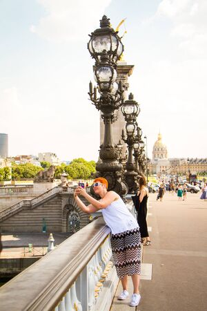 Paris, France - July 06, 2018: Tourist girl takes pictures of architectural elements and statues on Alexander the Third Bridge in Paris