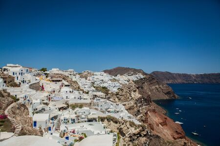 Oia town on Santorini island, Greece. View of traditional white houses and churches with blue domes over the Caldera, Aegean sea