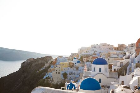 View of traditional white houses and churches with blue domes over the Caldera in Oia town on Santorini island, Greece Standard-Bild