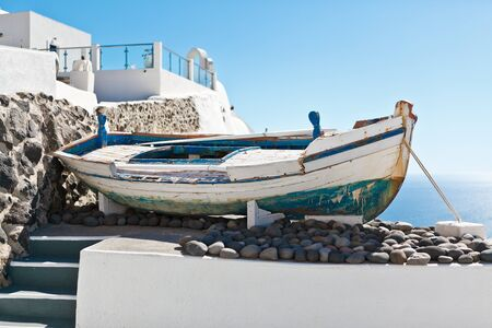 An old boat on a terrace with view on the white architecture of Santorini, Greece