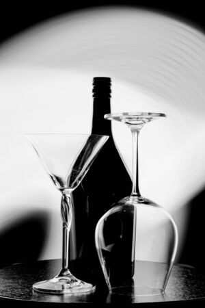 A black and white photo of a wine bottle and two glasses against the light spot on the black wall