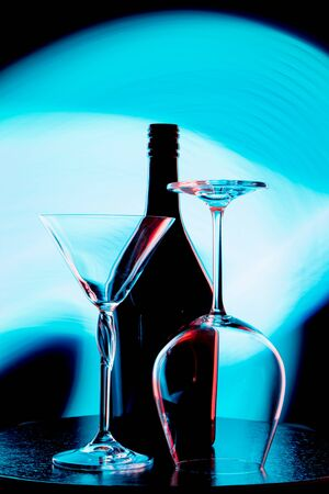 A photo of a wine bottle and two glasses against a light blue stain on a black wall Banco de Imagens