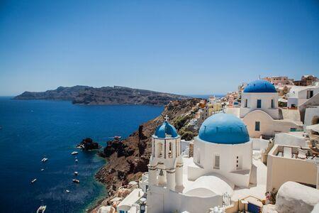 Oia-Stadt auf der Insel Santorini, Griechenland. Blick auf traditionelle weiße Häuser und Kirchen mit blauen Kuppeln über der Caldera, Ägäis?