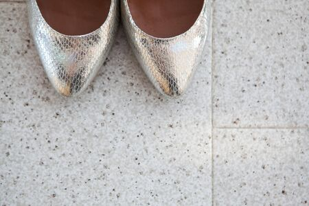 Closeup of the brides silver shoes toes on the marble floor