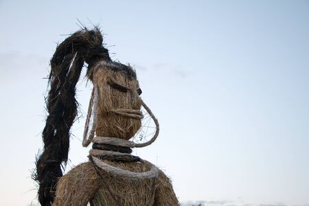 Close-up of the parts straw figure, the traditional decoration of the Slavic summer holiday over blue sky