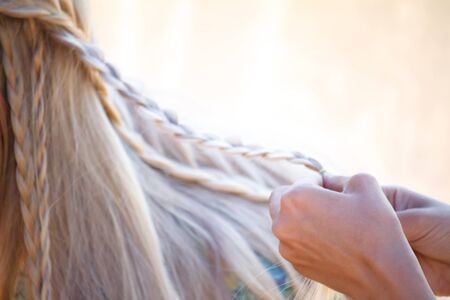 Closeup female graceful hands tangle blond hair in small pigtails