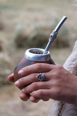 Womans hands hold traditional calabash gourds for yerba mate on the wooden surface, selective focus