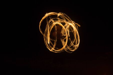 An artist shows a fire show at night spinning torches, circles of fire and loops Standard-Bild
