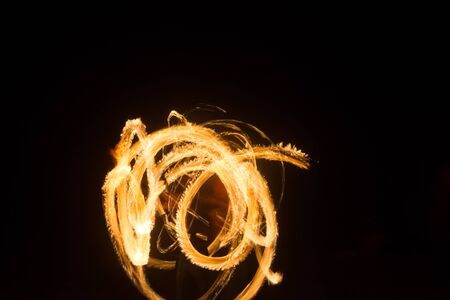 An artist shows a fire show at night spinning torches, circles of fire and loops Stockfoto