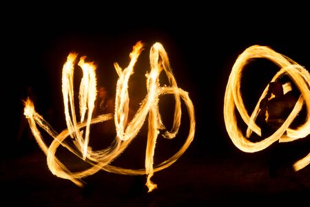 An artist shows a fire show at night spinning torches, circles of fire and loops 免版税图像